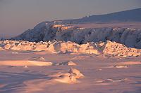 The low winter sun shines on pressure ice near Cape Dezhnev. Chukotka, Siberia, Russia.