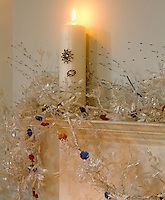 Transparent icy foliage wreaths a Christmas candle on a mantelpiece in the living room