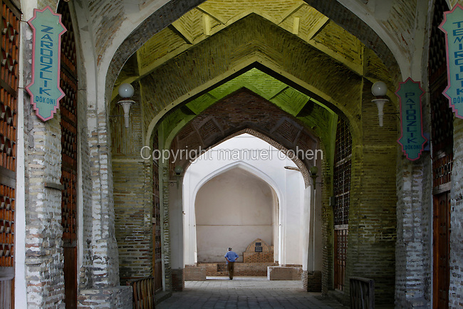 Low angle view through the arches of the Tok-i Tilpak Furushon Bazaar Bukhara, Uzbekistan, pictured on July 10, 2010 in the early morning. Tok-i Tilpak Furushon Bazaar, or the Capmaker's Bazaar is one of the remaining domed Bazaars originating in the 16th-17th century trading boom along the Silk Road. Here embroidered skullcaps were sold alongside books and manuscripts. The Bazaar is laid out in five spokes and contains the tomb of Holy Man Khoja Ahmed I Paran. Bukhara, a city on the Silk Route is about 2500 years old. Its long history is displayed both through the impressive monuments and the overall town planning and architecture. Picture by Manuel Cohen.