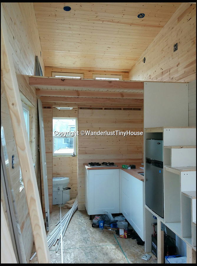 BNPS.co.uk (01202 558833)<br /> Pic: WanderlustTinyHouse/BNPS<br /> <br /> Well planned interior being constructed.<br /> <br /> Wanderlust for homebird's -  a young couple have solved the problem of leaving a much loved home to go travelling, by strapping a downsized version to the back of their pick-up and taking it with them.<br /> <br /> Patrick Howard and Lauren Kennedy ditched their office jobs, sold most of their worldly possessions and their 2,000 sq ft home and bought the miniscule 200 sq ft house, which can be towed by a pick-up truck.<br /> <br /> The pair, who were both electrical engineers, are now on their trip of a lifetime travelling all over the United States with their two dogs, Otis and Colbie.<br /> <br /> They are part of the Tiny House Movement - a growing group of people who are buying small houses and enjoying simpler lives.
