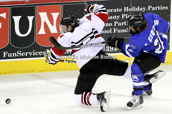 University of Nebraska Omaha's Kyle Ensign and UAH's Sebastian Geoffrion tangle while chasing the puck during the third period. UNO beat Alabama-Huntsville 4-0 Friday night at Qwest Center Omaha.  (Photo by Michelle Bishop)