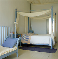 This bedroom is furnished with a simple four-poster bed painted blue draped with a sheer curtain