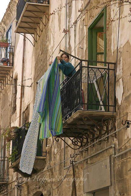 Sicilian woman hanging laundry out on balcony. Italy