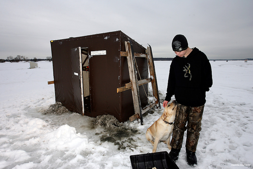 Smelt fisherman Travis MacDonald, 15, of Greenland with his dog 'Yeller' on Great Bay in Newington, N.H. Sunday,  January, 24, 2010.  (Portsmouth Herald Photo/Cheryl Senter)