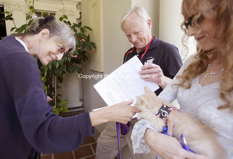 WASHINGTON, CT-- 21 July 2007--072107TJ12- Karin Bonjour, left, from New Milford, Conn., greets Luzon, a 3-month old domestic long hair cat, as Jim Lussier, center, with The Little Guild of St. Francis for the Welfare of Animals, checks the adoption form that Bonjour completed in hopes of bringing Luzon home during the opening of Sally Anderson-Bruce's display in the stairway gallery at the Gunn Memorial Library and Museum in Washington on Saturday, July 21, 2007.  Faith Falls, right, also with The Little Guild of St. Francis, holds Luzon. T.J. Kirkpatrick / Republican-American