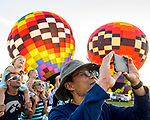 A near record crowd hot air balloon fans filled the hillsides at the National Balloon Classic launch field July 29 for opening ceremonies, balloon launches and music. Ming Lin of Ankeny points his cell camera one way even as balloons reach toward the sky behind him.
