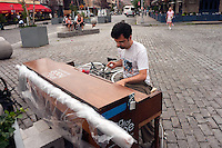 "New York, NY -  22 June 2010- A man plays ""Somewhere over the Rainbow"" with one hand while eating fresh strawberries with the other, in Gansvoort Plaza in the Meat Packing District of Manhattan... ""Play Me I'm Yours"" is a musical installation by British artist Luke Jerram who has been touring the project globally since 2008. From 9am-10pm each day, 60 pianos will be available to play across New York City. Presented by Sing for Hope they are located in public parks, streets and plazas the pianos will be available until 5th July for any member of the public to play and engage with."