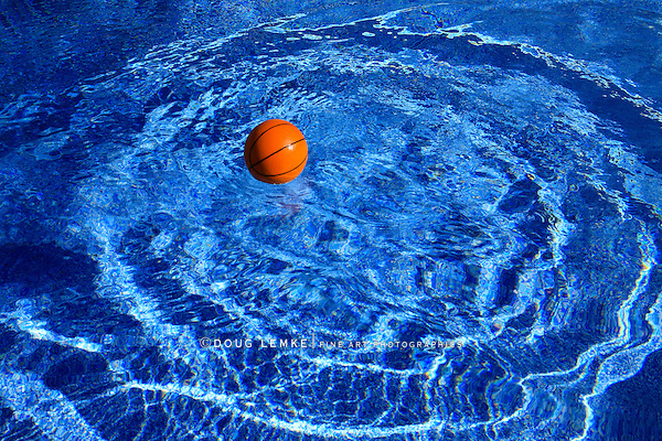 A Basketball Creates Concentric Ripples In Deep Blue Swimming Pool Water