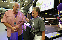 NWA Democrat-Gazette/DAVID GOTTSCHALK Bill Laney (left), teacher at Fayetteville High School, smiles with Martha Thornton, with Fayetteville Public Schools, Wednesday, August 7, 2019, after receiving a gift for teaching more than 30 years following the Fayetteville Public Schools annual Convocation ceremony in Bulldog Arena on the Fayetteville High School campus. The event, which features performances by students, informational presentations and awards, serves as a kickoff to the school year which begins Tuesday in Fayetteville.