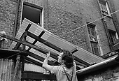 Roof repairs on an outbuilding at 5 Carol Street, one of a row of squatted houses in Camden Town, London, which was later granted short-life status and subsequently became a council-supported housing co-operative.