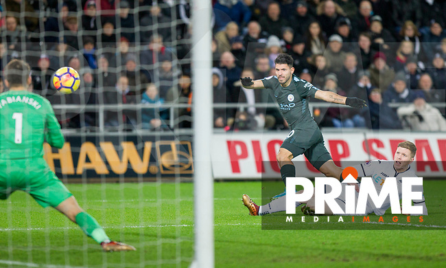 Sergio Aguero of Manchester City shoots at goal under pressure from Alfie Mawson of Swansea City during the EPL - Premier League match between Swansea City and Manchester City at the Liberty Stadium, Swansea, Wales on 13 December 2017. Photo by Mark  Hawkins / PRiME Media Images.
