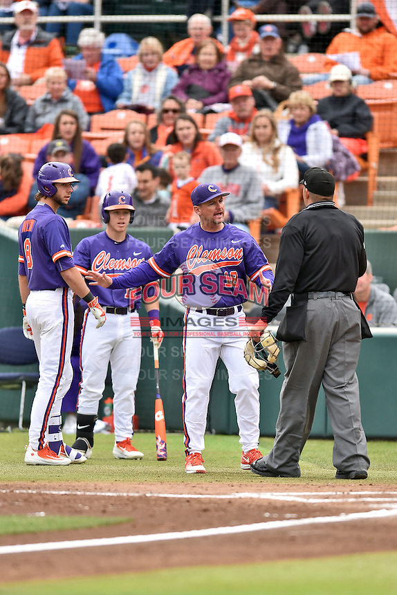 Clemson Tigers manager Monte Lee (18) discusses a play with home plate umpire Jay Pierce as Weston Wilson (8) and Robert Jolly (12) look on during a game against the Maine Black Bears at Doug Kingsmore Stadium on February 20, 2016 in Clemson, South Carolina. The Tigers defeated the Black Bears 9-4. (Tony Farlow/Four Seam Images)