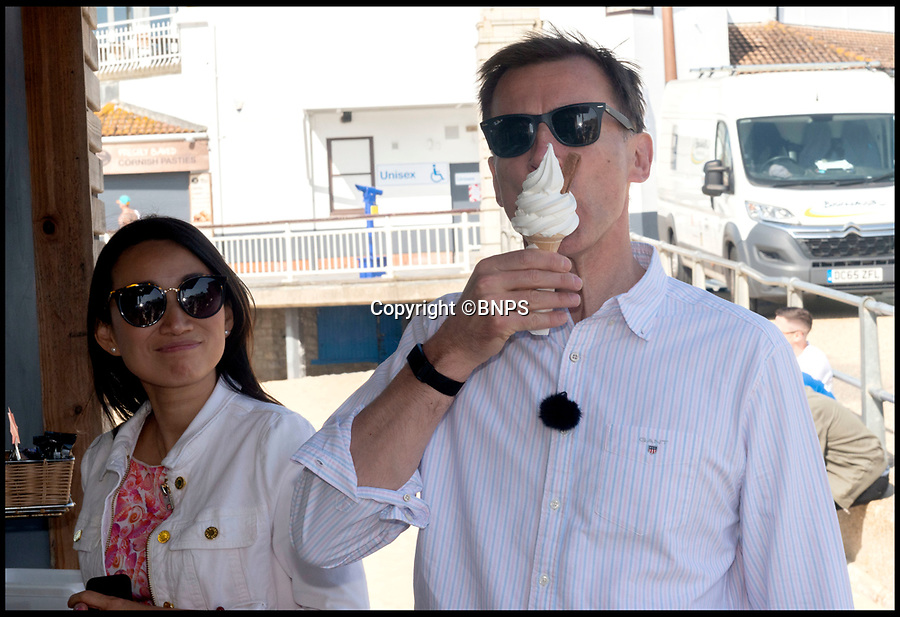 BNPS.co.uk (01202 558833)Pic:   RogerArbon/BNPS<br /> <br /> Jeremy Hunt licks an ice cream by the pier in Bournemouth this morning with his wife Lucia Hunt watching.