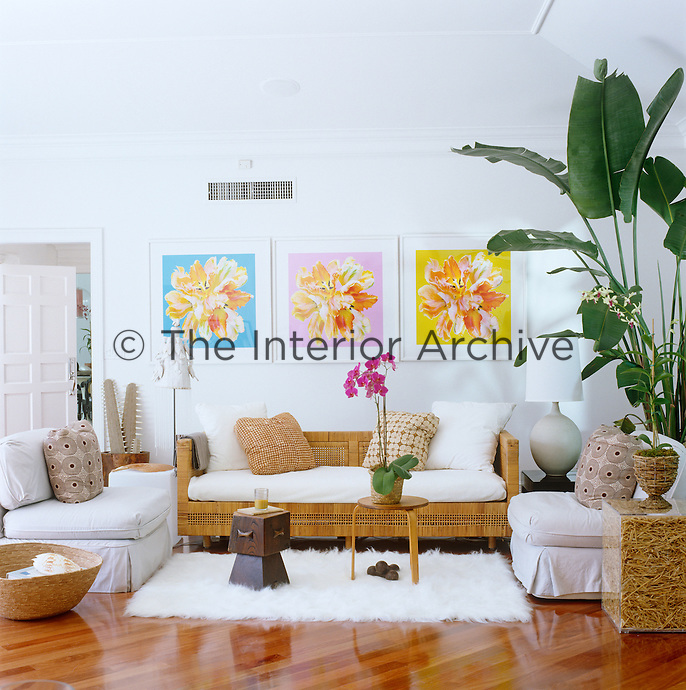 In the living room the set of brightly coloured prints above the vintage wicker sofa are works by Alexandra Penney