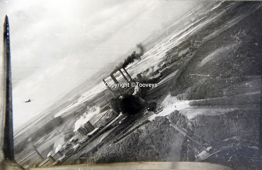 BNPS.co.uk (01202 558833)<br /> Pic:  Tooveys/BNPS<br /> <br /> Taken on 12/08/41 - the power station at Knapsack, Cologne, after the first bombs had been dropped during a daylight raid by Blenheims.<br /> <br /> Dramatic photos showing a series of heart-pounding World War Two bombing raids from the pilot's perspective have come to light.<br /> <br /> They were taken from Blenheim bombers undertaking attacks on targets in Germany and Nazi-occupied Netherlands in 1941.<br /> <br /> Several capture the immediate aftermath of a direct hit, with flames and clouds of smoke signifying they had achieved their aim.<br /> <br /> The album, which contains almost 100 photos, has emerged for sale with Toovey's Auctions, of Washington, west Sussex.