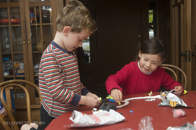 Berkeley CA Boy, five, and girl, seven, in friendly interaction while building fantasy park with soft clay  MR