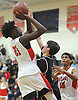 Julius Goddard #21 of Amityville, left, hits a contested jumper during a Suffolk County varsity boys basketball game against Sayville at Amityville High School on Thursday, Jan. 5, 2017. Amityville won by a score of 81-73.