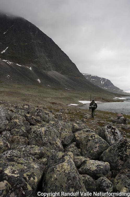 Mann på vei langs Langvatnet. Store Langvasstinden skjult i tåke ----- Man walking in mountain terrain
