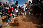 Family and friends cover a grave with dirt during a mass funeral for 20 people, killed during fighting between opposition rebels and loyalist forces of Col. Muammar Qaddafi, in Benghazi, Libya, March 20, 2011. The main hospital in Benghazi reported around 50 dead fighters and civilians the previous day and at least 35 on Sunday.