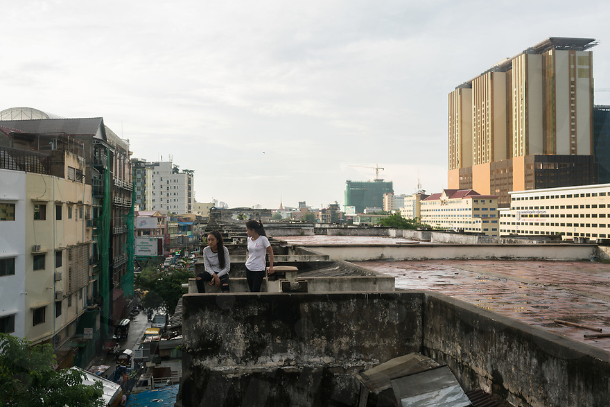 June 10, 2017 - Phom Penh (Cambodia). Two young girls stare at the people moving out their belongings from the rooftop of the White Building. After months of negotiation most of the families living in here received a compensation and the iconic building from the '60 will be demolished to make space to a new condo. © Thomas Cristofoletti / Ruom