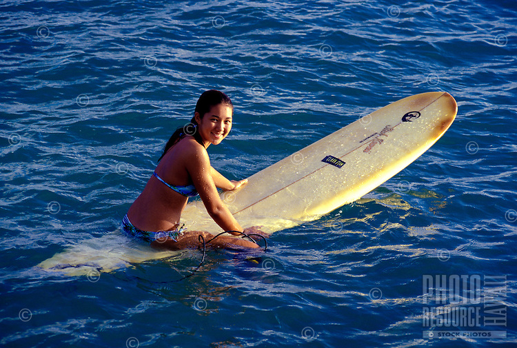 A smiling young teenaged girl straddles her surfboard waiting for a wave in the blue water off Waikiki Beach.