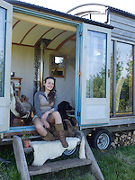 Willow De La Roche sits in the entrance of her shepherd's hut in the company of Homer, a black Labrador