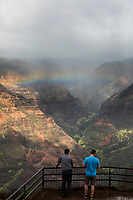 Two men enjoy the overview of Wamea Canyon with a rainbow, Kaua'i.