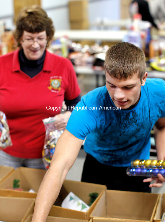 Oakville, CT- 07, November 2010-110710CM02 Richard Difederico III, of Watertown, fills care packages that will be shipped overseas to US Soldiers, Sunday afternoon at the Oakville VFW. Behind him is his grandmother, Phyllis Schaar, who is a member of the Ladies Auxiliary of Oakville VFW Post 7330, who also headed up the event. 100's of boxes were packed and planned to be shipped overseas.    Christopher Massa Republican-American