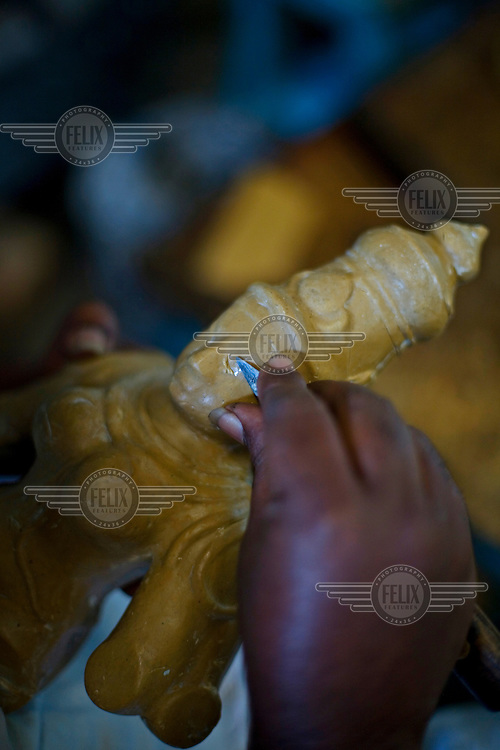A worker carves a wax mould of an icon in the S. Devasenapathy Sthapathy and Sons bronze casting workshop. The current Sthapathy generation is the twenty-third generation of bronze casters. Their method using the lost-wax process remains unchanged to this day.
