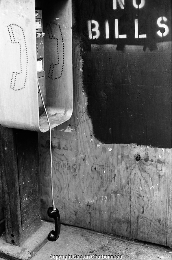 A public telephone with it receiver hanging off the hook