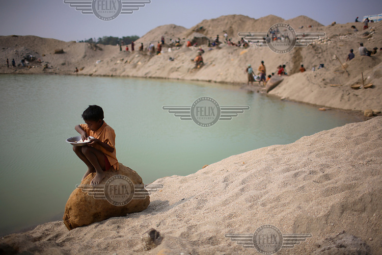 A child worker eats his lunch. At least 10,000 people, including 2,500 women and over 1,000 children, are engaged in stone and sand collection from the Bhollar Ghat on the banks of the Piyain river. Building materials such as stone and sand, and the cement which is made from it, are in short supply in Bangladesh, and commands a high price from building contractors. The average income is around 150 taka (less than 2 USD) a day...