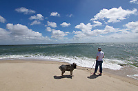 Sylt, Germany. Ellenbogen, the Northern tip of the island. Man with Eurasian dog.
