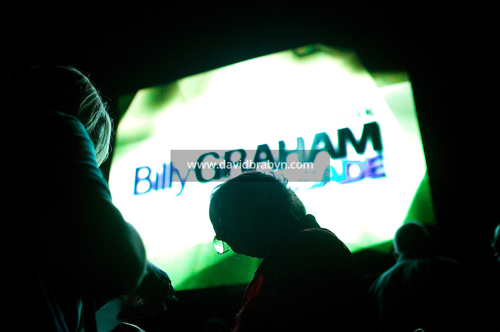 "Standing by a giant screen, counselor Joanne Borchers (L) takes Mirta Ferrin (C) through the process of ""commiting to God"" at the end of the first day of evangelist Billy Graham's three-day New York crusade at Flushing Meadows-Corona Park in Queens, NY, USA, Friday June 24 2005."