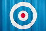 Target/roundel painted on blue corrugated building.