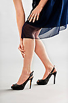 Woman standing in high heels with hands on leg