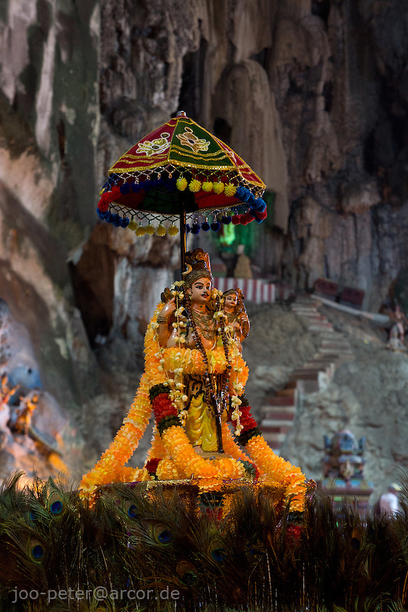 woman carrying metal pot with holy milk while Thaipusam ceremonies inside Batu Caves, Kuala Lumpur, Malaysia, 2012. Thaipusam ceremonies, celebrated by tamile Hindu community in Malaysia, take place  in Sanctuary of Batu Caves at the border of Kuala Lumpur, each year around end of January or beginning of February, according to Hindu moon calendar. The event is paying hommage to Lord Murugan, a spirit or god created by Shiva to lead the army of gods against the army of evil demons, finally defeating the evil spirits. There are many ways to present offerings or sacrifices for this major religious event. Devotees mortify their bodies by carrying heavy kavaris with spears fixed in their skin or fruits, flowers and little post with holy milk fixed with hooks in their skin, ascending the stairways to the sanctuary in trance, `followed by assistant  taking care and musicians playing loud and fast rhythmic trance music.  Many families shave their head in a ritual before ascending the stairways, as part of rituals to obtain salvation for their ancestors.
