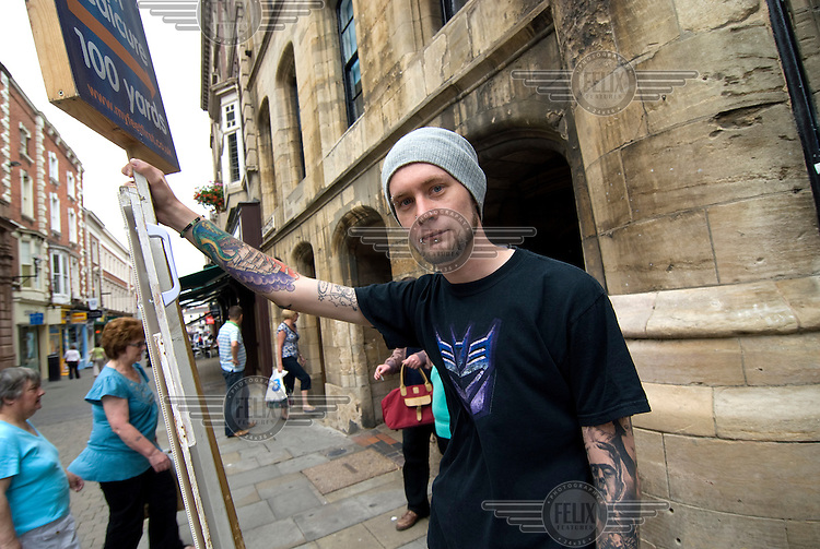 A young man with tattoos and piercings holds a sign directing the public to a location 100 yards away in Lincoln.
