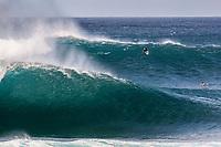 Surfers paddle over a big set at Pipeline (off of 'Ehukai Beach Park), North Shore, O'ahu.