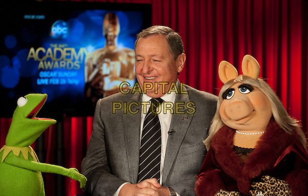 Kermit the Frog, Academy President Tom Sherak, and Miss Piggy promoting the 84th Academy Awards during a satellite tour held at HD Vision Broadcast Center in Studio City, CA on Thursday, February 23, 2012.  The 84th Academy Awards® will be presented on Sunday, February 26, 2012, at the Hollywood & Highland Center®, and televised live by the ABC Television Network..* Editorial Use Only*.oscars  half length grey gray suit muppets .CAP/A.M.P.A.S./NFS.©A.M.P.A.S. Supplied by Capital Pictures.