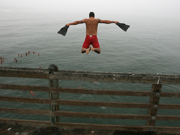O.pier.1.0702.jl.jpg/photo Jamie Scott Lytle/Oceanside Lifeguard Sgt. Blake Faumuina jumps off the Oceanside Pier Wednesday morning during a traditional pier jump before the big 4th. of  July week.