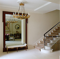 An elaborate carved and gilded chandelier makes a statement in an otherwise understated entrance hall