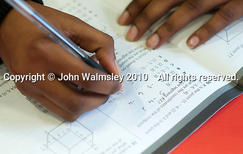 Writing answers in a maths exercise book, state secondary school.