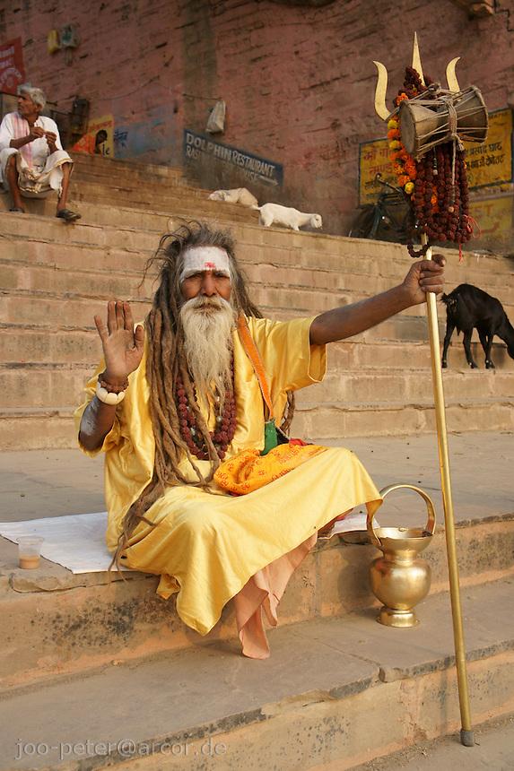 Sadhu, follower of Shiva on the stairs  of the main Ghat of river Ganga in Varanasi (Dashaswamedh Ghat)