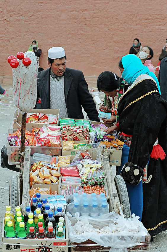 A muslim seller from the Hui minority is speaking with two tibetan women in front of the Main Assembly Hall in the monastery of Labrang, the first day of the Great Prayer (Monlam Chenmo). Xiahe, China, 09 March 2007.