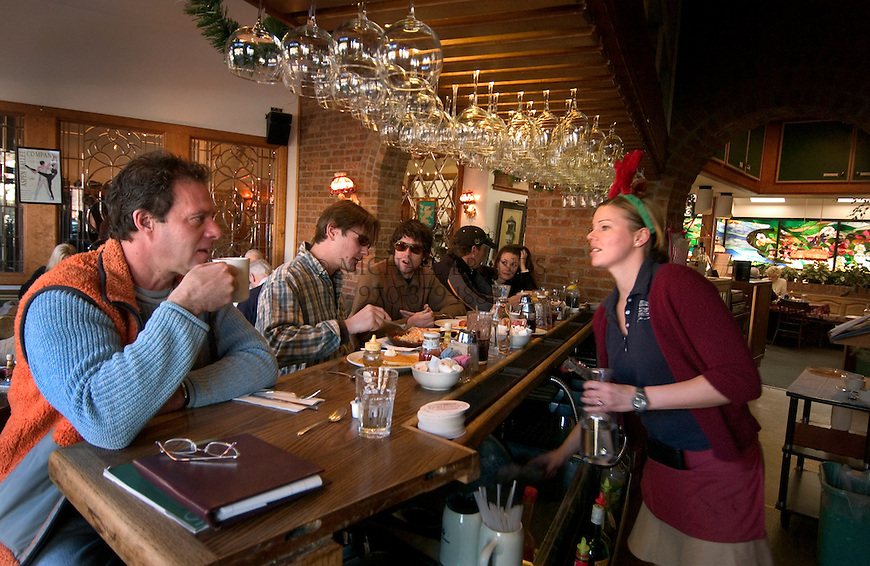 On the right, waitress Richenda Rosslee, from South Africa, chats with diners at the bar of the Wienerstube restaurant in Aspen, CO. © Michael Brands.