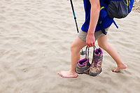 Legs of barefoot girl walking on sandy beach carrying hiking boots, Sand Point, Olympic National Park, Olympic Peninsula, Clallam County, Washington, USA