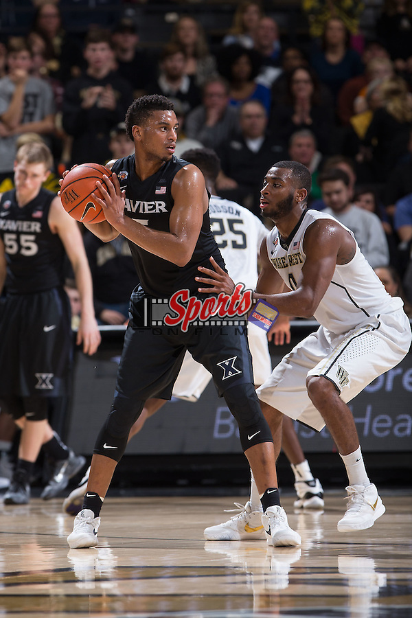 Trevon Bluiett (5) of the Xavier Musketeers is guarded by Codi Miller-McIntyre (0) of the Wake Forest Demon Deacons during first half action at the LJVM Coliseum on December 22, 2015 in Winston-Salem, North Carolina.  The Musketeers defeated the Demon Deacons 78-70.  (Brian Westerholt/Sports On Film)