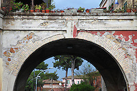 In the Saint Eurosia place of  the Garbatella quarter, in Rome, a closed up view of a beautiful old arc. On the other side of it, one can distinguish the top of some of the typical buildings of this characteristic group of houses that dates back to 1920, together with some trees (in particular pines) , and some street-lamps. Digitally Improved Photo.
