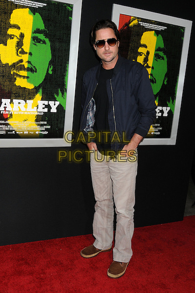 "Luke Wilson.""Marley"" Los Angeles Premiere held at Arclight Cinemas, Hollywood, California, USA..April 17th, 2012.full length top black blue jacket grey gray trousers sunglasses shades hands in pockets .CAP/ADM/BP.©Byron Purvis/AdMedia/Capital Pictures."