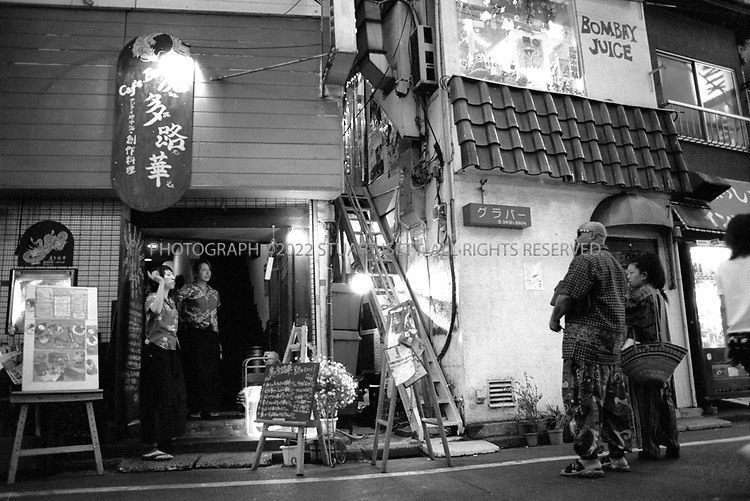 "8/10/2002--Shimokitazawa, Tokyo, Japan..Bars, cafes and restaurants stay open late in Shimo...Wedged between Tokyo's Shinjuku and Shibuya wards, Shimokitazawa's maze of narrow streets form the ramparts of all that is non-conformist in get-along, go-along Japan. In ""Shimokita,"" old village shops trade happily beside newer, eccentric clothing stores, funky restaurants, matchbox playhouses and live-music clubs. The unpretentious ambience is a magnet for students and other young visitors for whom Tokyo's usual street fashion scene has become more fascist than fun and mainstream entertainment is, well, too mainstream. Musicians, designers, aspiring actors and other would-be iconoclasts have settled the area, as have young professionals opting for a less-structured lifestyle. ...All photographs ©2003 Stuart Isett.All rights reserved.This image may not be reproduced without expressed written permission from Stuart Isett."